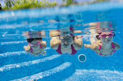 Underwater family in swimming pool. Mother with two kids swimming underwater in pool Royalty Free Stock Photos