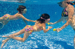 Underwater family in swimming pool. Mother teaching her kids to swim underwater in pool Stock Photo
