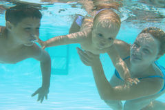 Underwater family in swimming pool. Royalty Free Stock Image