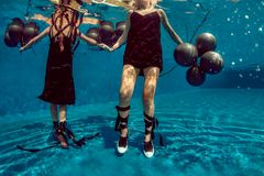 Underwater fashion shoot with black baloons Royalty Free Stock Images