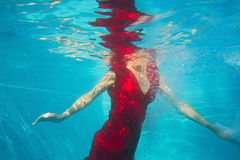 Underwater fashion. Fashion woman in red dress underwater Royalty Free Stock Photos