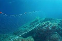 Underwater sea fishing net gillnet on the seabed. Underwater a fishing net gillnet fixed on rocks on the seabed, Mediterranean sea, Costa Brava, Spain stock photos