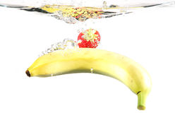 Underwater Fruits. A strawberry and a banana thrown in the water, on white background Royalty Free Stock Photos