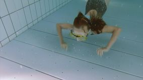 Underwater girl in aquapark. Child submerging under water. Happy little girl wearing mask learning how to swim underwater in the pool at aquapark. Kid having fun stock footage