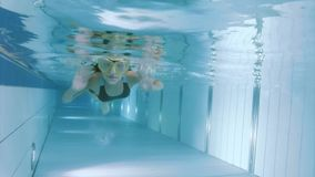 Underwater girl in aquapark. Child submerging under water. Happy little girl wearing mask learning how to swim underwater in the pool at aquapark. Kid having fun stock video footage