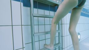 Underwater girl in aquapark. Underwater footage clip of little girl exiting the pool. Child feet on stairs under water stock video footage