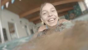 Underwater girl in aquapark. Happy little girl 10 year old learning how to swim in the pool at aquapark. Kid having fun at the leisure center - swimming and stock video