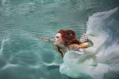 Underwater girl. Beautiful red-haired woman in a white dress, swimming under water. Nymph or mermaid, fantasy concept royalty free stock image