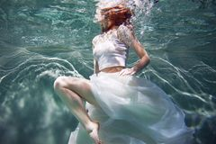 Underwater girl. Beautiful red-haired woman in a white dress, swimming under water. Nymph or mermaid, fantasy concept stock image