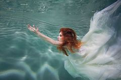 Underwater girl. Beautiful red-haired woman in a white dress, swimming under water. Royalty Free Stock Photo