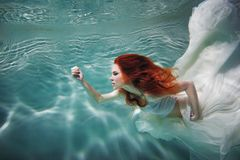 Underwater girl. Beautiful red-haired woman in a white dress, swimming under water. stock photos