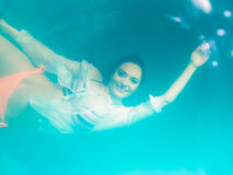 Underwater girl wearing bikini in swimming pool Stock Photos
