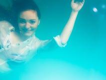Underwater girl wearing bikini in swimming pool Stock Photos