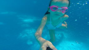 Underwater happy beautiful girl in swimming pool having fun. On family summer vacation stock video footage