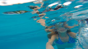 Underwater happy beautiful girl in swimming pool having fun. On family summer vacation stock video