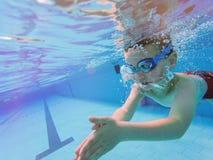 Underwater happy little boy in swimming pool swimmnig laps stock image