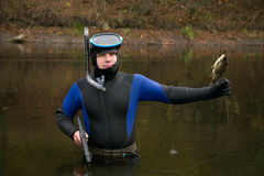 Underwater hunter. Hunter has killed very small fish, it is forbidden Royalty Free Stock Image