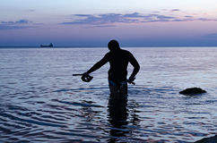 Underwater hunter on the beach preparing to dive. Fishing in the Black sea . Royalty Free Stock Photography