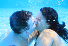 Underwater kiss. Loving couple kissing underwater in the swimming pool Royalty Free Stock Images
