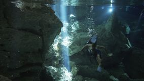 Divers in cave. Underwater landscape, man in swimsuit with fins dive from camera in stream of sun and make many bybbles, group of snorkeling people swiming with stock footage