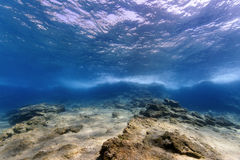 Underwater Landscape. An underwater landscape with a rocky bottom. Water surface to see on top of image, splashing waves in the middle. This is a underwater Stock Image