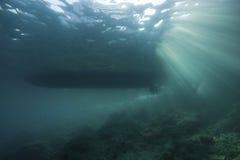 Underwater landscape with sun rays. Underwater landscape with diveboat, a stony reef and sun-rays passing through Stock Photo