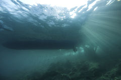 Underwater landscape with sun rays. Underwater landscape with diveboat, a stony reef and sun-rays passing through Stock Image