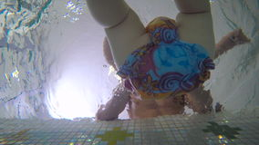 Underwater: the little kid splashing the water in the child pool stock video footage