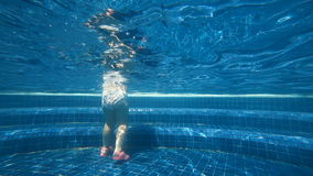 Underwater little steps. Rear view of unrecognizable child walking on the bottom of swimming pool stock footage