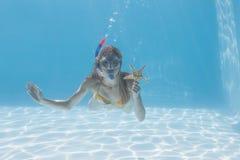 Underwater louro bonito na piscina com tubo de respiração e estrela do mar imagens de stock