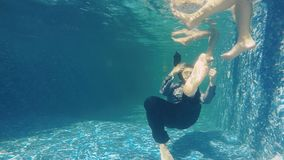 Man in suit shows thumbs up under water near moving female legs. Underwater. Man moves his feet in front of camera and shows thumbs up. Female legs are moving stock footage