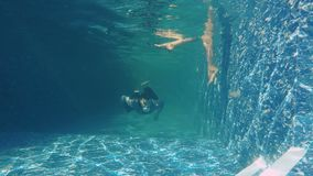 Man in suit swims under water with piece of paper in his mouth. Underwater. Man swims forward on camera. The bearded guy holds a piece of paper in his mouth stock video footage