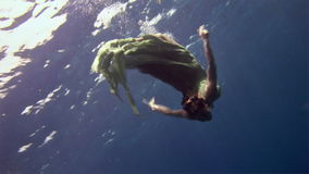 Underwater model free diver in fairy costume on background of corals in Red Sea. stock footage