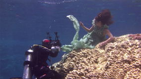 Underwater model free diver poses for camera on background of corals in Red Sea. Filming a movie. Young girl smiling. Extreme sport in marine landscape, coral stock video footage