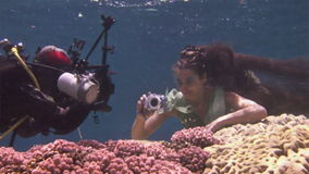 Underwater model free diver poses for camera on background of corals in Red Sea. Filming a movie. Young girl smiling. Extreme sport in marine landscape, coral stock footage