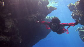 Underwater model free diver in red dress on background of corals in Red Sea. Filming a movie. Young girl smiling at camera. Extreme sport in marine landscape stock footage