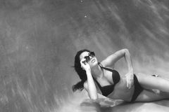 Underwater Model. Sassy image of a woman swimming underwater in a bikini and sunglasses Royalty Free Stock Image