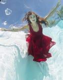 Underwater modelo en un vestido rojo Foto de archivo