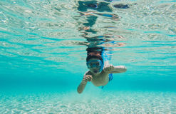 Underwater nature study. Boy snorkeling in clear blue sea Stock Images