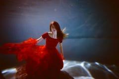 Underwater nello stagno con acqua più pura Bella ragazza in color scarlatto del vestito e capelli scorrenti Fotografia Stock