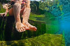 Underwater photo of child bare feet in natural swimming pool. Royalty Free Stock Images