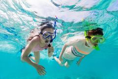 Kids on vacation. Underwater photo of cute kids swimming in a tropical ocean water during summer vacation royalty free stock photography