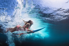 Underwater photo of girl with board dive under ocean wave. Young girl in bikini - surfer with surf board dive underwater with fun under big ocean wave. Family royalty free stock image