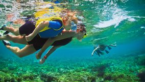 Underwater photo. Happy family snorkelling in tropical sea. Happy family - father, mother, kids in snorkeling mask dive underwater with tropical fishes in coral royalty free stock photo