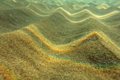 Underwater photo - light refracted on sea surface forming rainbows on small sand 'dunes' in shallow water near beach. Abstract ma royalty free stock photos