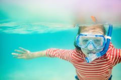 Little girl snorkeling. Underwater photo of a little girl swimming in tropical ocean Royalty Free Stock Photos