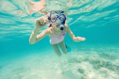 Little girl snorkeling. Underwater photo of a little girl swimming in tropical ocean Stock Photography