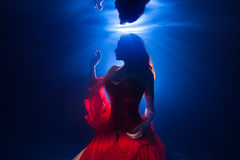 Underwater photo pretty young girl  with dark long hair wearing Stock Photography