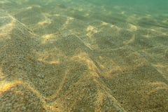 Underwater photo, sea bottom in shallow water, sun shining, light refracting on sand dunes. Abstract marine background stock image