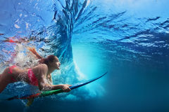 Underwater photo of surfer girl diving under ocean wave. Young girl in bikini - surfer with surf board dive underwater under big ocean wave Family lifestyle Stock Photography